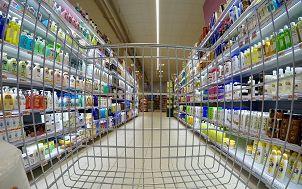 wózek sklepowy w sklepie spożywczym jadący między regałami wypełnionymi produktami