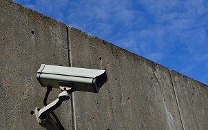 kamera monitoringu umieszczona na żelbetonowej ścianie. W tle niebieskie niebo.