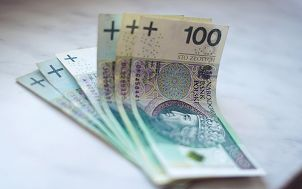 na zdjęciu plik rozłożonych banknotów stuzłotowych leżących na białej powierzchni