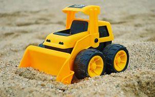 na piasku stoi zółtoczarny zabawkowy spychacz