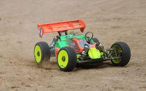 poglądowy zabawkowy, kolorowy samochodzik sterowany zdalnie jadący po piasku
