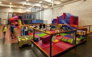Pełna kolorów sala zabaw dla dzieci. Na pierwszym planie wyłożona kolorowymi matami ogrodzona część dla najmłodszych dzieci. Dalej znajdują się różne instalacje dla starszych dzieci. (Obraz Eirin z Pixabay)