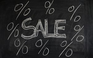 """zdjęcie przedstawia czarną tablicę z napisem wykonanym białą kredą o treści """"SALE"""" i umieszczonymi obok znakami """"%"""""""